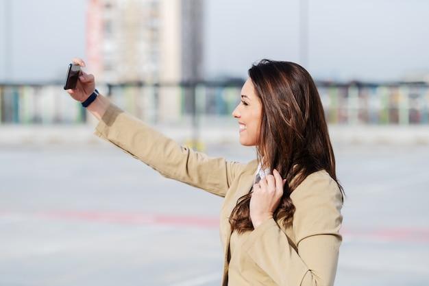 Boczny widok piękna caucasian brunetka w beżowy kurtki stać plenerowy i brać selfie.