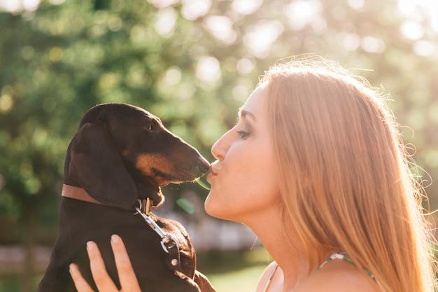 Boczny widok piękna młoda kobieta całuje jej psa