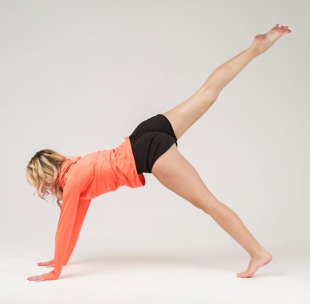 Boczny widok podnosi jej nogę up sportowa kobieta