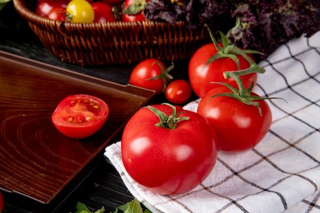 Boczny widok pomidory na szkockiej kraty płótnie i rżnięty pomidor w tacy na drewnianym stole
