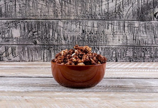 Boczny widok popkorn w pucharze na biały drewniany stołowy horyzontalnym