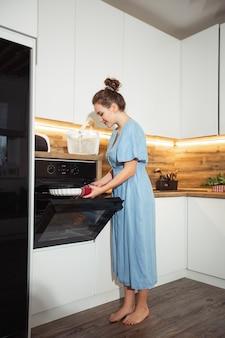 Boczny widok powabna caucasian kędzierzawa blond kobieta w fartuchu bierze out od piekarnika piec jedzenie. wnętrze kuchni domowej. kobieta biorąc blachę do pieczenia. koncepcja domowej roboty gotowania.