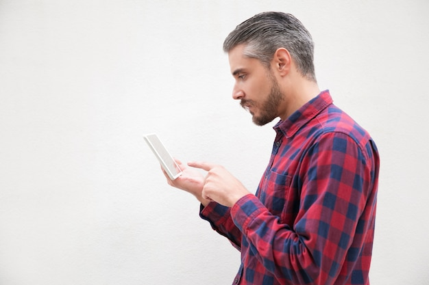 Boczny widok poważny brodaty mężczyzna używa pastylka komputer osobistego