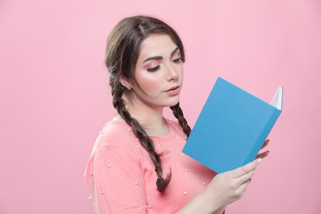 Boczny widok pozuje kobieta podczas gdy czytający książkę