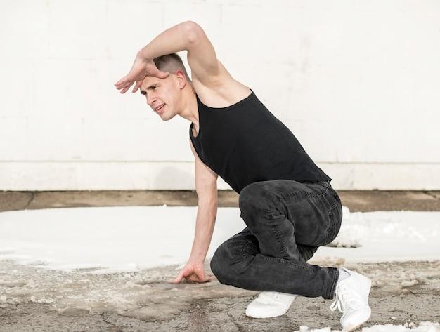 Boczny widok pozuje męski tancerz podczas gdy tanczący
