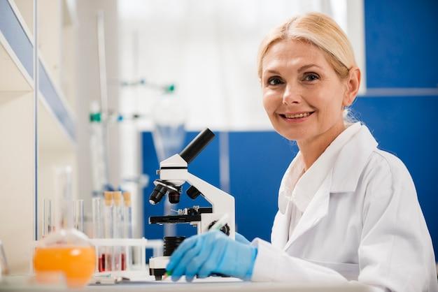 Boczny widok pozuje w lab z mikroskopem i chirurgicznie rękawiczkami żeński naukowiec