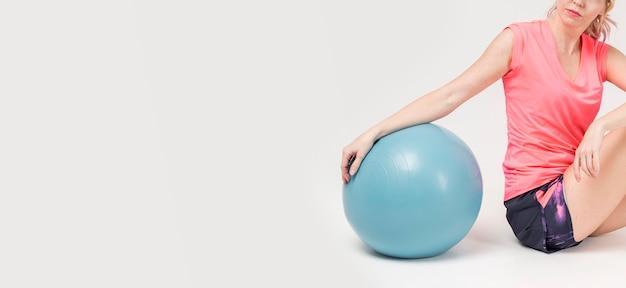 Boczny widok pozuje z ćwiczenie piłką i kopii przestrzenią kobieta