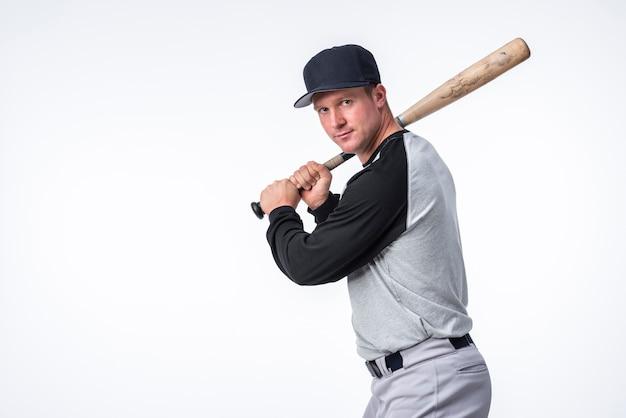 Boczny widok pozuje z kijem bejsbolowym mężczyzna