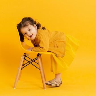 Boczny widok pozuje z krzesłem śliczny dziecko