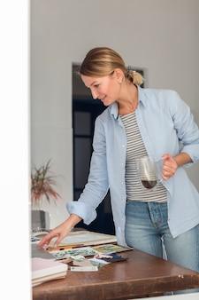 Boczny widok pracuje kobieta podczas gdy trzymający kubek