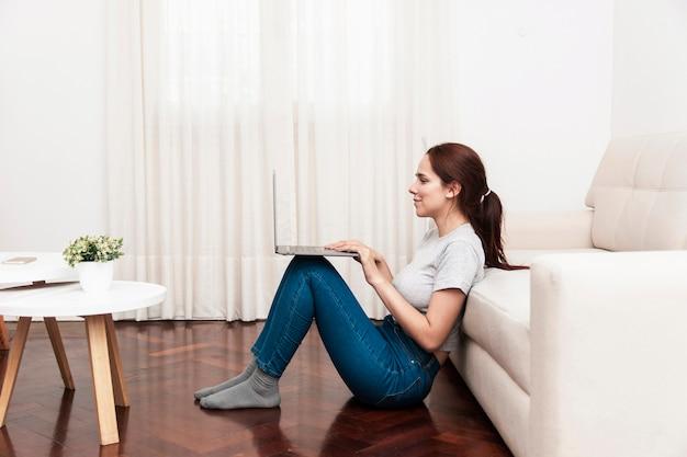 Boczny widok pracuje na laptopie kobieta