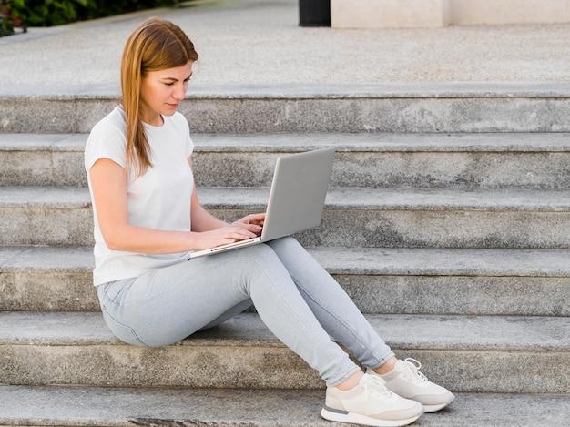Boczny widok pracuje na laptopie na krokach kobieta
