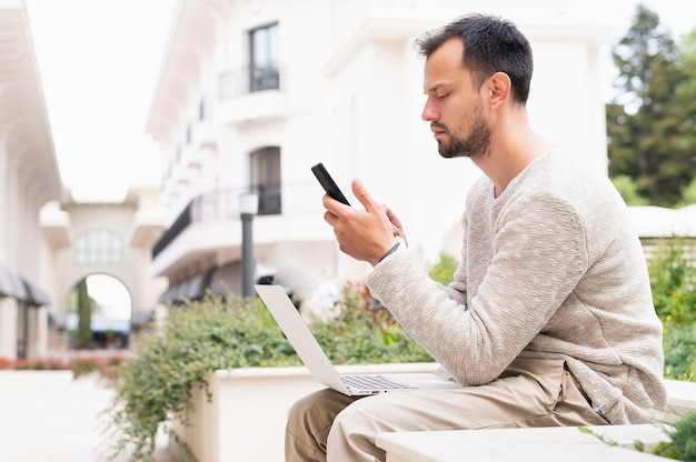 Boczny widok pracuje na smartphone i laptopie mężczyzna outdoors