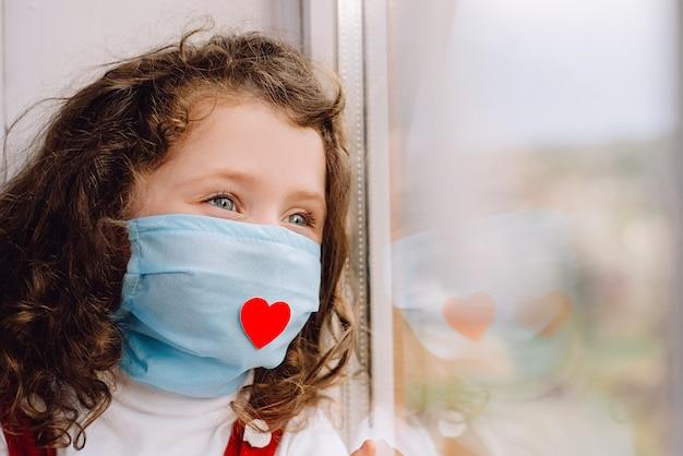Boczny widok preschool dziewczyna w ochronnej twarzy masce z czerwonym sercem, siedzący na parapecie w domu, patrzejący outside zamazanego okno. koncepcja dziękuje wszystkim niezbędnym pracownikom podczas pandemii covid-19