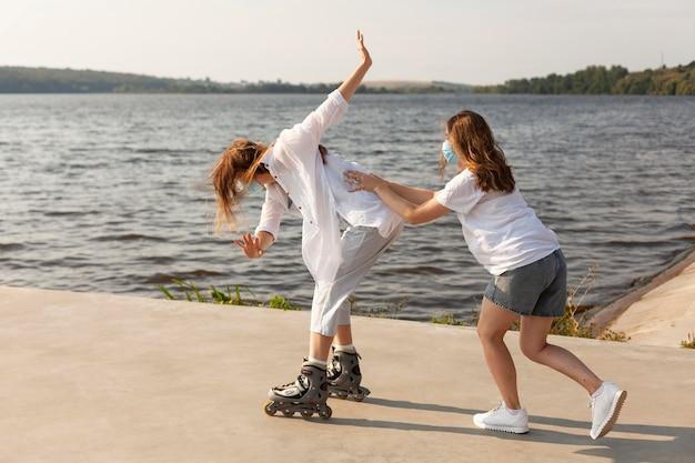 Boczny widok przyjaciół bawiących się nad jeziorem na rolkach