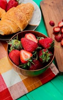 Boczny widok puchar truskawki z półksiężyc rolką w talerzu na płótnie na zielonym stole