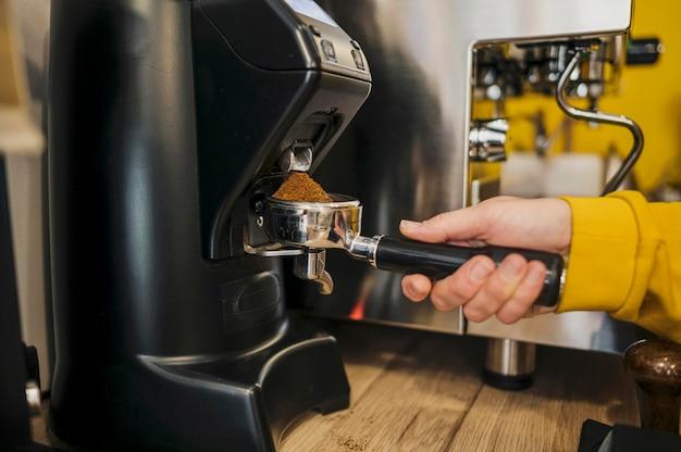 Boczny widok robi kawie przy kawową maszyną barista