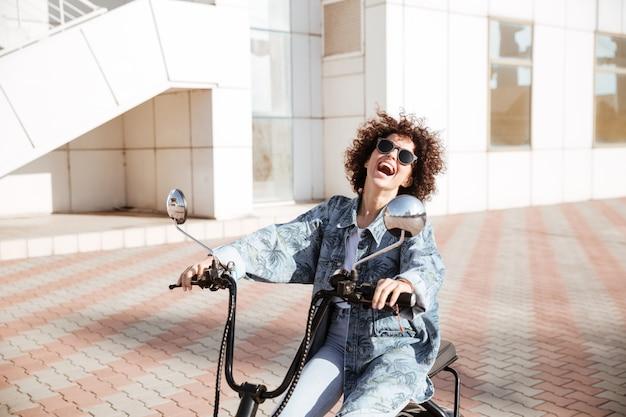 Boczny widok roześmiana kędzierzawa kobieta w okularach przeciwsłonecznych pozuje na nowożytnym motocyklu outdoors
