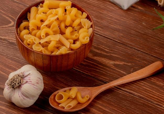Boczny widok różni macaronis w drewnianym pucharze i łyżce z czosnkiem na drewnianym stole