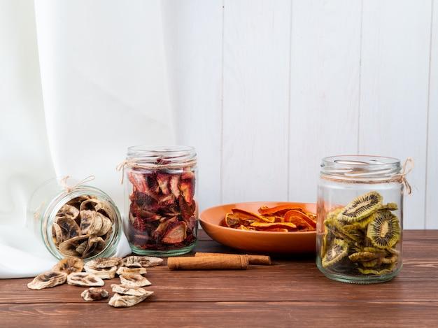 Boczny widok różnorodne wysuszone pokrojone owoc w szklanych słojach bananowy kiwi i truskawka na drewnianym tle