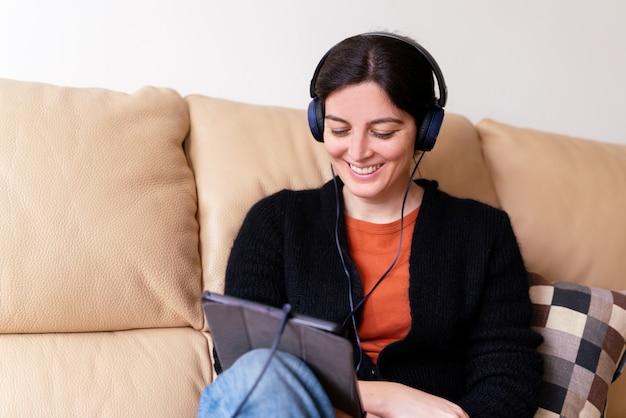 Boczny widok rozochocona kobieta dzwoni chorego przyjaciela z urządzeniem elektronicznym z hełmofonami. społeczny dystansowy pojęcie w kwarantanny izolacji w domu.
