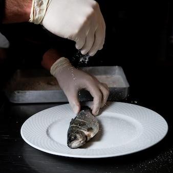 Boczny widok ryba z podeszwą i ludzką ręką w bielu talerzu