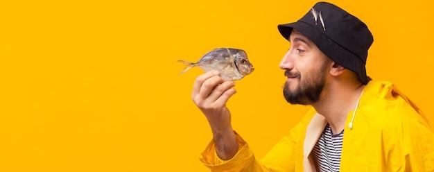 Boczny widok rybaka mienia chwyt z kopii przestrzenią