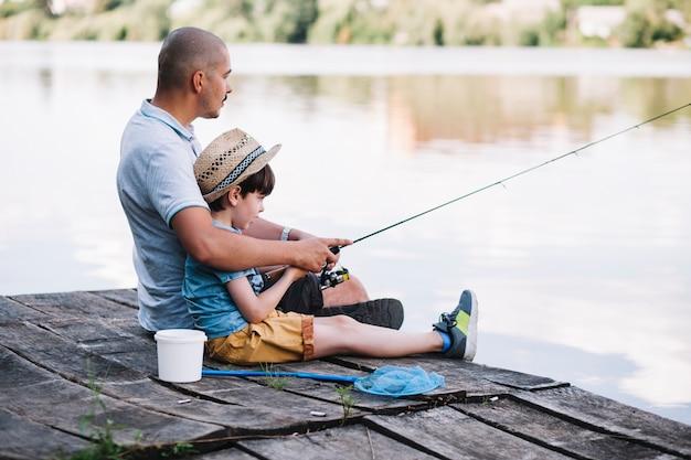 Boczny widok rybaka obsiadanie na molu z jego syna połowem na jeziorze