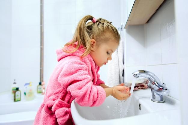 Boczny widok śliczna mała dziewczynka myje jej ręki z kucykiem w różowym szlafroku.
