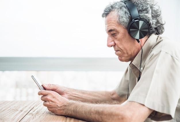 Boczny widok słucha muzykę na hełmofonie starszy mężczyzna patrzeje telefon komórkowego