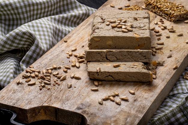 Boczny widok smakowici plasterki chałwa z słonecznikowymi ziarnami na drewnianej desce
