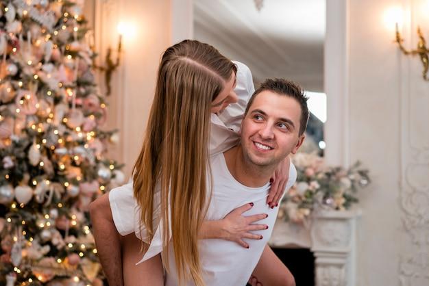 Boczny widok smiley mężczyzna piggybacking kobiety