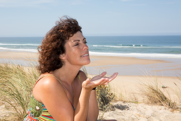 Boczny widok spokojny kobiety obsiadanie na piaskowatej plaży
