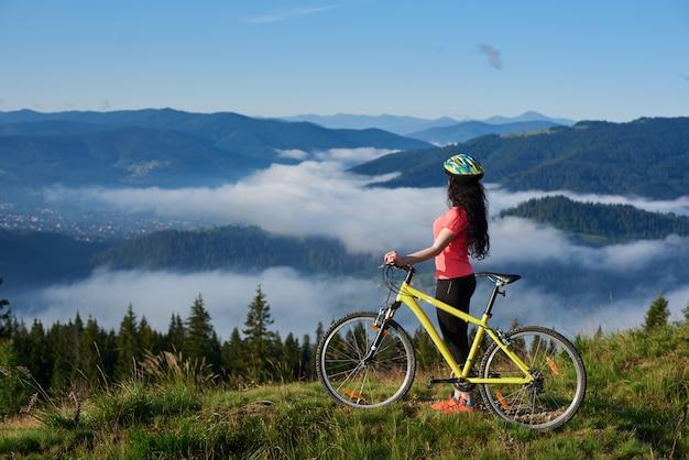 Boczny widok sportowy żeński rowerzysta z żółtym bicyklem w górach, w ranku. mgliste góry, lasy na niewyraźne tło