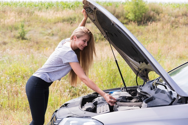 Boczny widok sprawdza silnik na drodze kobieta