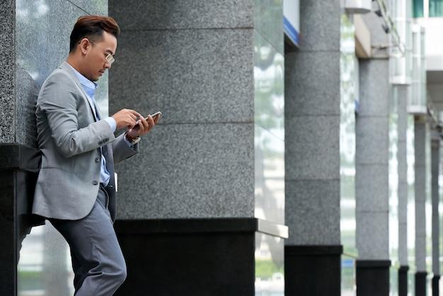 Boczny widok sprawdza smartphone przy przerwa na lunch mężczyzna outdoors