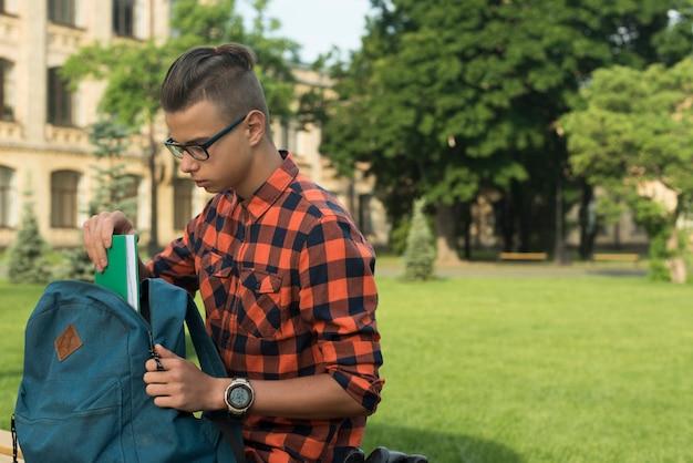 Boczny widok średni strzał nastoletni chłopak stawia książkę w plecaku