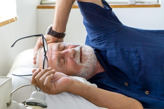 Boczny widok starego człowieka dosypianie na łóżku