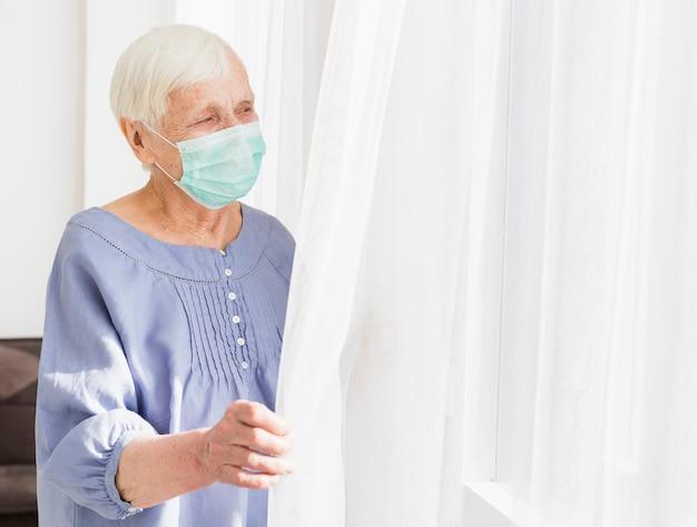 Boczny widok starsza kobieta patrzeje przez okno z medyczną maską