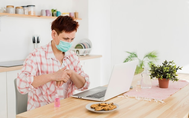 Boczny widok starsza kobieta z medyczną maską używać ręki sanitizer przed pracować na laptopie