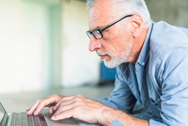 Boczny widok starszy mężczyzna używa laptop
