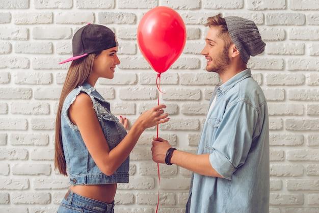 Boczny widok stylowa nastoletnia para w cajgów ubraniach.