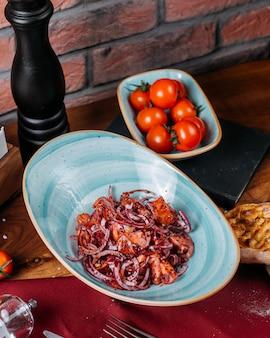 Boczny widok świeża sałatka z siekającymi czerwonej cebuli pomidorami i sumakh na stole