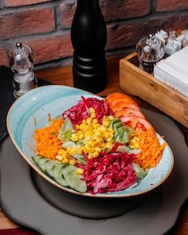 Boczny widok świeża sałatka z siekanymi kapuścianymi marchewkami ogórków pomidorami i kukurudzą w talerzu