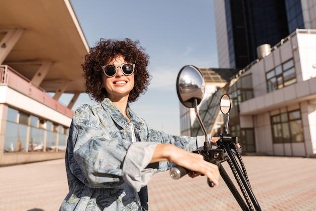 Boczny widok szczęśliwa kobieta w okularach przeciwsłonecznych pozuje na motocyklu