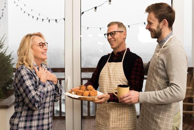 Boczny widok szczęśliwa rodzina z muffins i filiżanką
