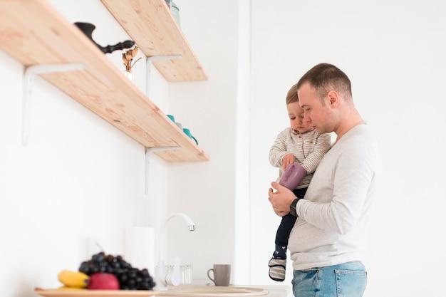 Boczny widok tata mienia dziecko w kuchni