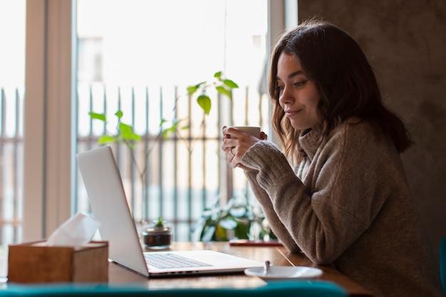 Boczny widok trzyma filiżankę i patrzeje laptop kobieta