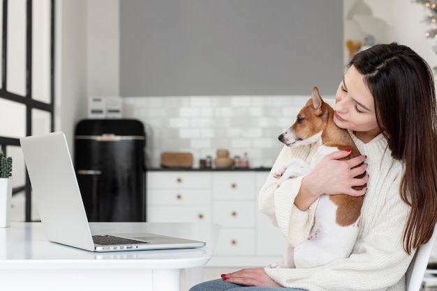 Boczny widok trzyma jej psa kobieta podczas gdy patrzejący laptop