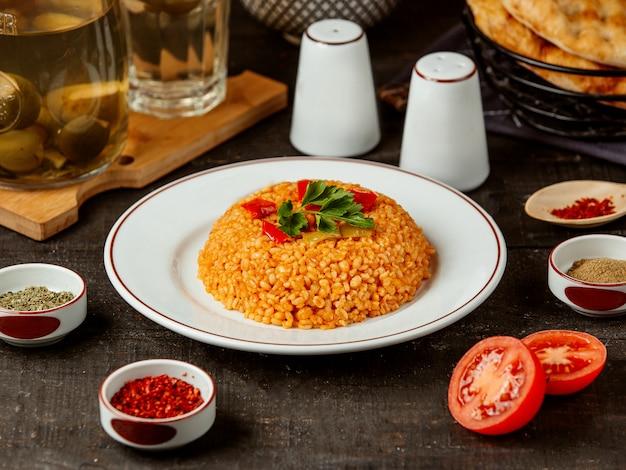 Boczny widok turecki kuchni bulgur z warzywami na talerzu